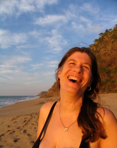 an image of a lady on a beach laughing.
