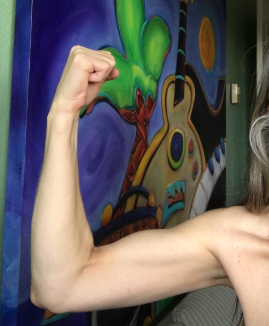 an image of the arm of a woman who has been doing pushups and you can see her flexing her right bicep